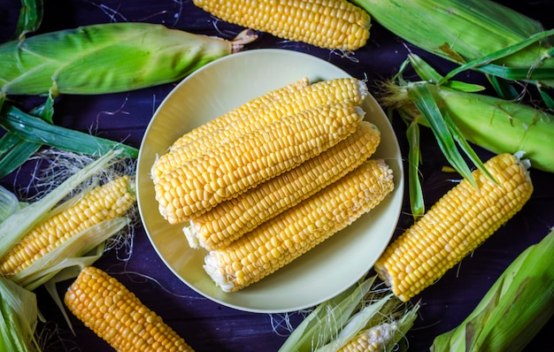 Gepeld jonge maïs op tafel gedeeltelijk gepeld