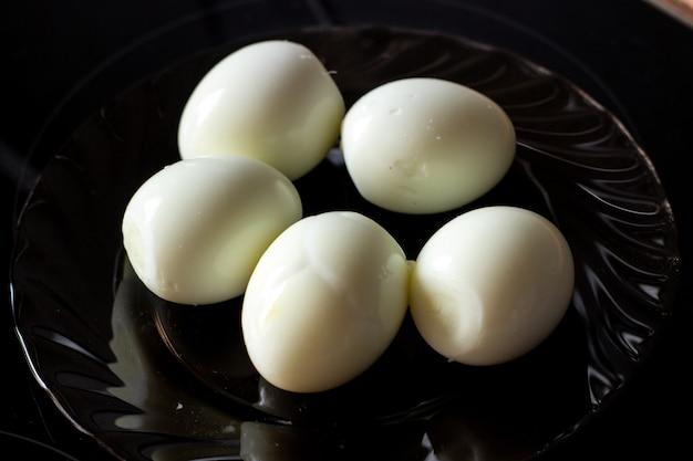 Gepelde eieren op een zwarte plaat