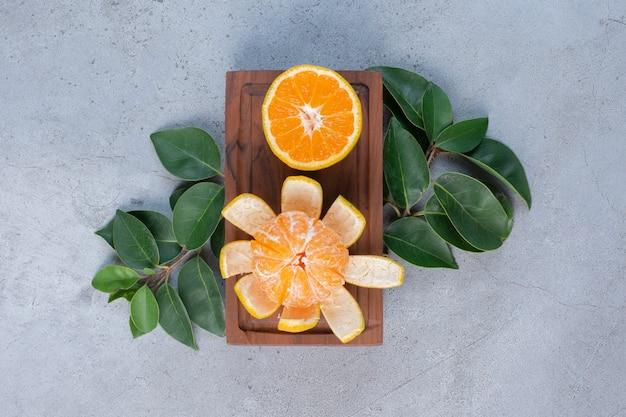 Gepelde en gesneden mandarijnen op een klein bord op marmeren achtergrond.