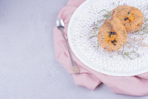 Gepelde en gesneden peer met kruiden en specerijen in een witte plaat