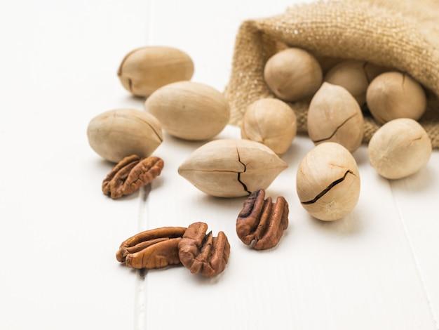 Gepelde en ongepelde pecannoten worden uit een zak op een witte tafel gemorst