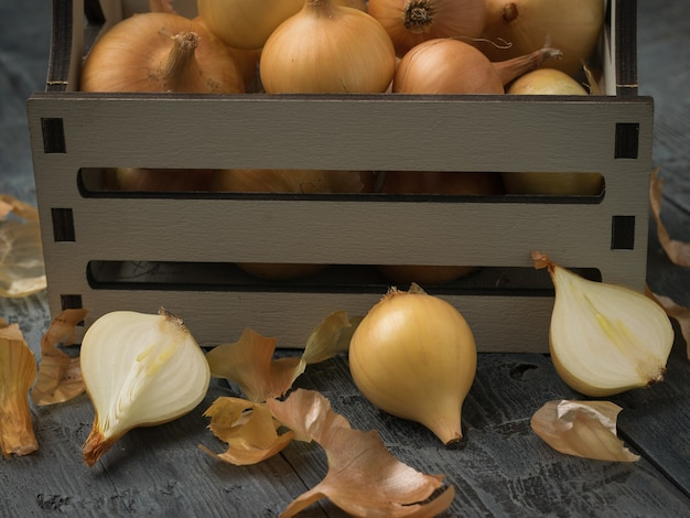 Gepelde en ongeschilde uien in de buurt van een houten kist op een houten tafel.