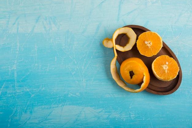 Gepelde gele oranen in een houten schotel, bovenaanzicht