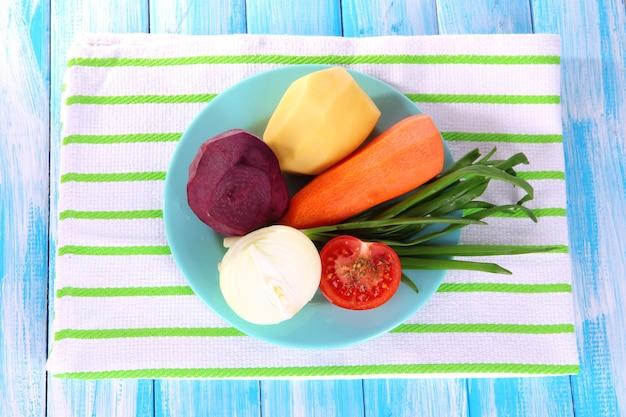 Gepelde groenten op plaat op servet