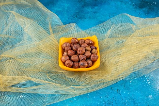 Gepelde hazelnoten in een kom, op tule, op de blauwe tafel.