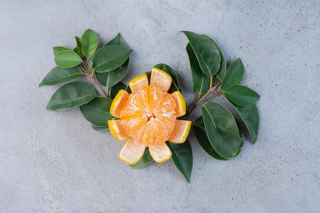 Gepelde mandarijn en decoratieve bladeren op marmeren achtergrond.