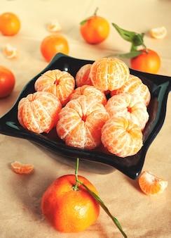 Gepelde mandarijnen in een zwart diep bord omgeven door mandarijnen en stukjes gepelde mandarijn.