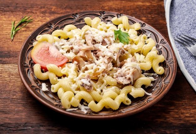 Gepelde mosselen met pasta op een donkere houten ondergrond.