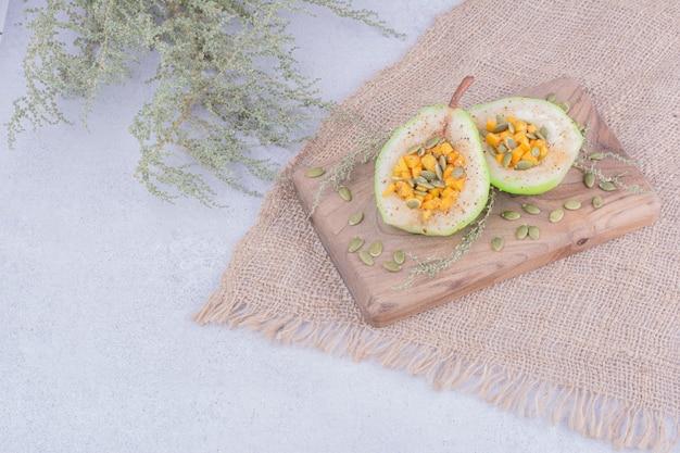 Gepelde perensalade met wortel en pompoenpitten op een houten bord