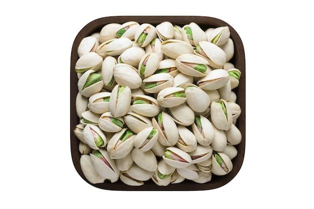 Gepelde pistachenoten in vierkante kom geïsoleerd op een witte achtergrond. biologisch voedsel, bovenaanzicht.