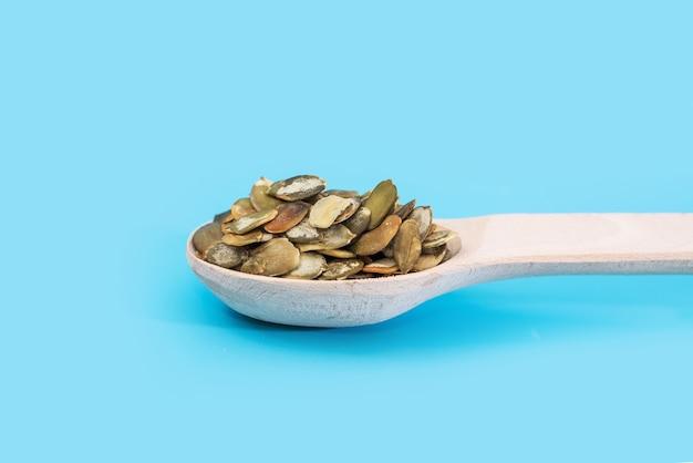 Gepelde pompoenpitten in een houten lepel op een blauwe tafel.