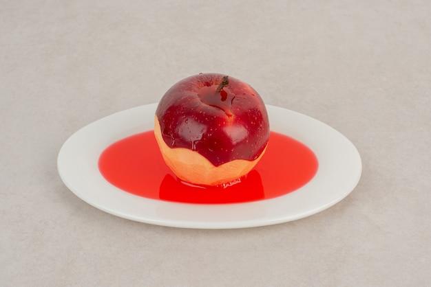 Gepelde rode appel op sap op witte plaat.