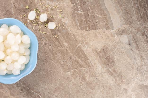 Gepelde teentjes knoflook op een stenen tafel.