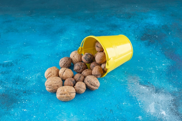 Gepelde walnoten in een emmer, op de blauwe tafel.