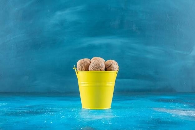 Gepelde walnoten in een emmer op het blauwe oppervlak