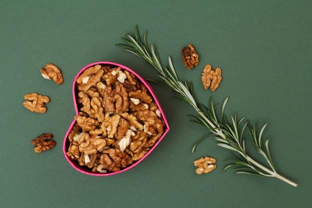 Gepelde walnoten in geschenkdoos in de vorm van een hart met rozemarijn op een groene achtergrond. nuttig voedzaam eiwitproduct. viering dag concept. bovenaanzicht.