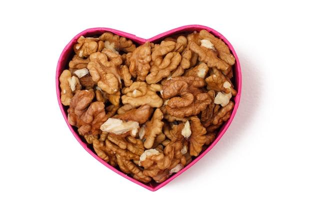 Gepelde walnoten in geschenkdoos in de vorm van een hart op een witte geïsoleerde achtergrond. nuttig voedzaam eiwitproduct. viering dag concept. bovenaanzicht.