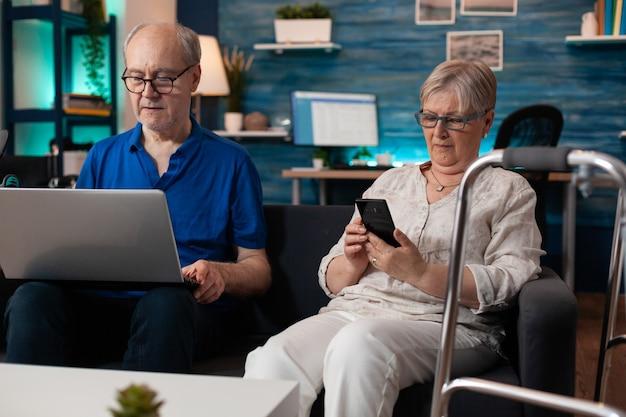 Gepensioneerd bejaarde echtpaar met smartphone en laptop