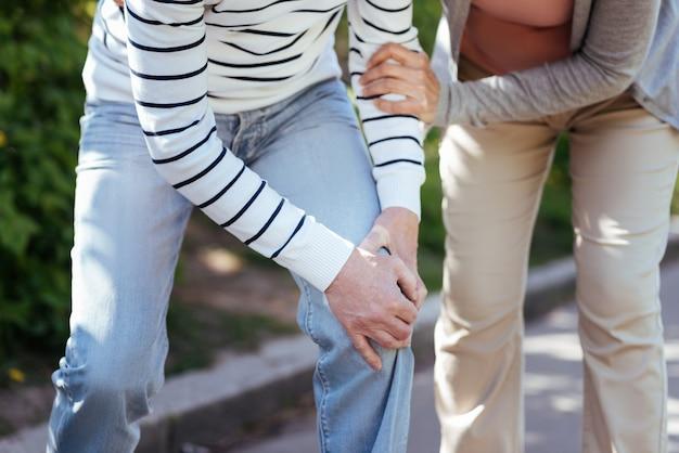 Gepensioneerd betrokken ziek paar dat pijn in de gewrichten voelt en elkaar ondersteunt terwijl ze buiten genieten van het weer