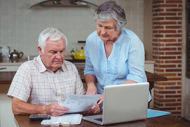 Gepensioneerd echtpaar het berekenen van rekeningen met laptop
