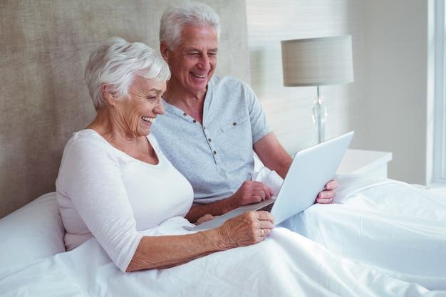 Gepensioneerd echtpaar met behulp van laptop zittend op bed