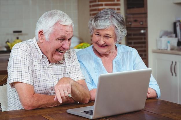 Gepensioneerd echtpaar met behulp van laptop