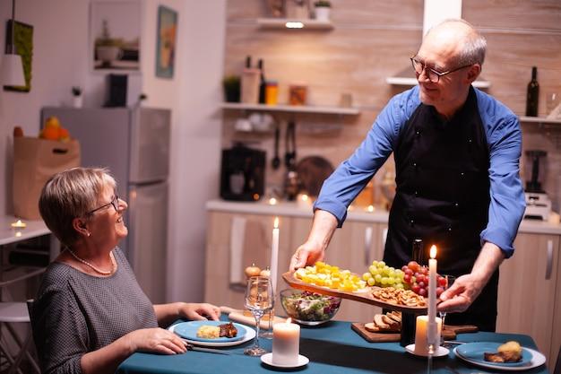 Gepensioneerd koppel lacht naar elkaar in de keuken tijdens relatieviering. bejaard oud echtpaar praten, aan de tafel in de keuken zitten, genieten van de maaltijd,