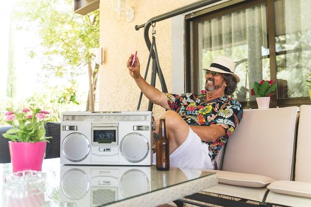 Gepensioneerd met mobiele telefoon tijdens het luisteren naar muziek.