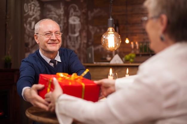 Gepensioneerd oud stel dat plezier heeft tijdens het diner. echtgenoot die haar vrouw een gift geeft.