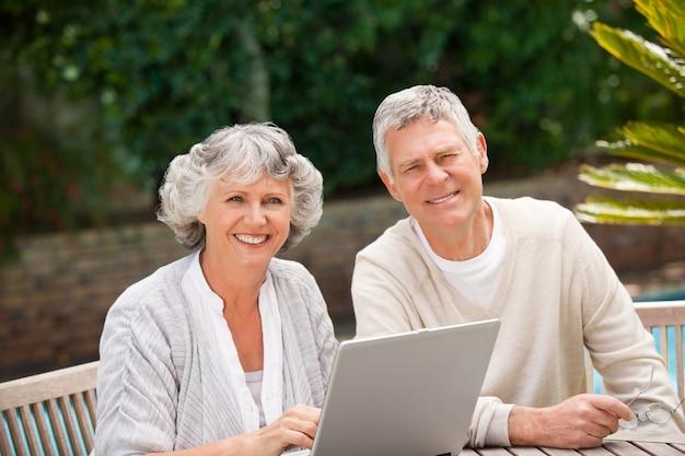 Gepensioneerd paar dat aan hun laptop werkt