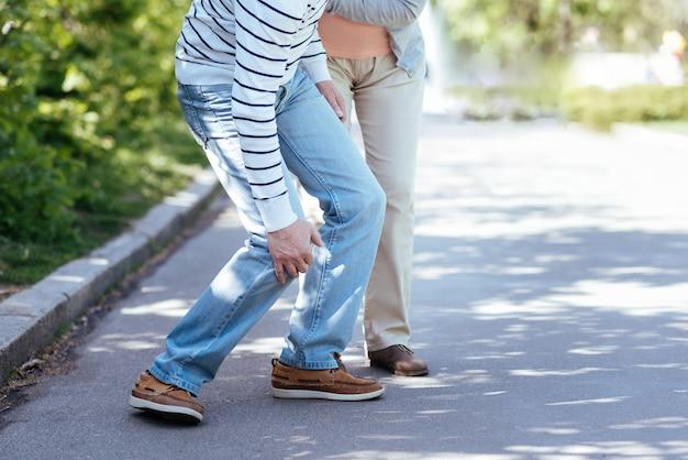 Gepensioneerde behulpzame oude vrouw die om zieke man geeft en hem ondersteunt terwijl hij buiten staat