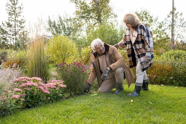 Gepensioneerde blonde vrouw in brillen en warme stijlvolle geruite jas helpt haar man op de knieën op groen gazon bij bloembed