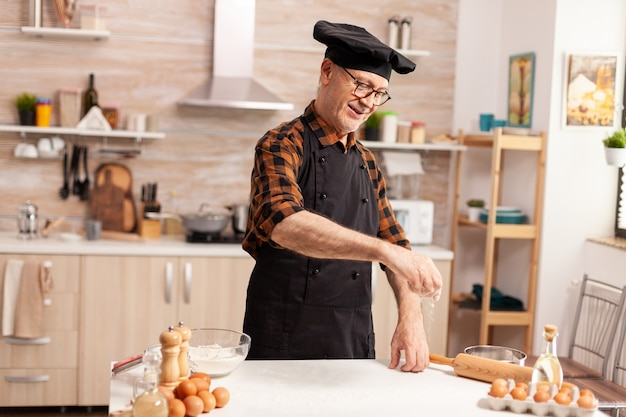 Gepensioneerde chef-kok in huiskeuken die tarwebloem over tafel verspreidt terwijl hij handgemaakte cook f bereidt met bonete en schort, in keukenuniform die zeven ingrediënten met de hand bestrooit.
