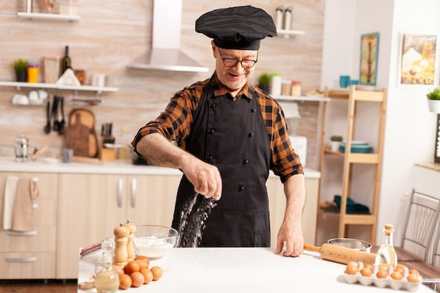 Gepensioneerde chef-kok in huiskeuken met schort terwijl hij ingrediënt op tafel besprenkelt voor lekkers