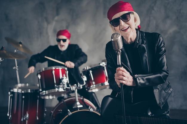 Gepensioneerde dame man rock populaire band groep uitvoeren concert zingen