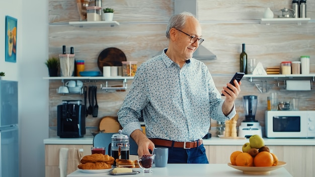 Gepensioneerde die muziek luistert op mobiele telefoon terwijl hij geniet van een kopje koffie tijdens het ontbijt in de keuken. gelukkig ontspannen oudere senior dansen, leuke levensstijl met moderne technologie
