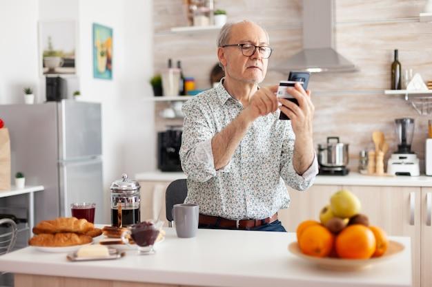 Gepensioneerde die online betaalt met creditcard en applicatie van smartphone tijdens het ontbijt in de keuken. gepensioneerde bejaarde die internetbankieren gebruikt om thuis te betalen met moderne technologie
