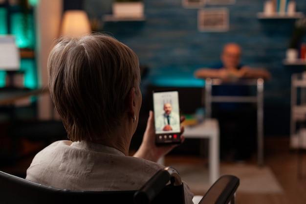 Gepensioneerde gehandicapte vrouw in gesprek met dokter tijdens videogesprek