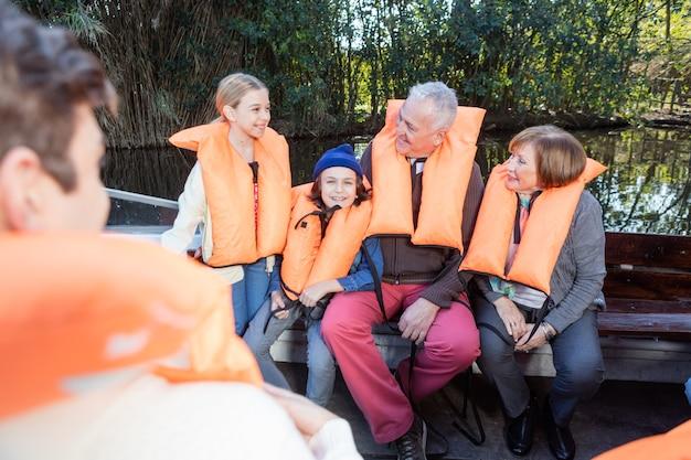 Gepensioneerde grootouders met kleinkinderen lachen op de boot