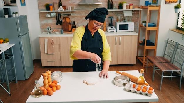 Gepensioneerde huisvrouw met bonete en keukenschort die gezeefde bloem op het deeg toevoegt. oudere senior bakker met uniform besprenkelen, zeven, verspreiden van ingrediënten met de hand bakken zelfgemaakte pizza en brood.
