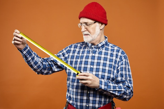 Gepensioneerde kaukasische klusjesman of arbeider die een bril, een rode gebreide muts en een geruit overhemd draagt en meetlint vasthoudt tijdens renovatie, metingen verricht, serieuze geconcentreerde blik heeft