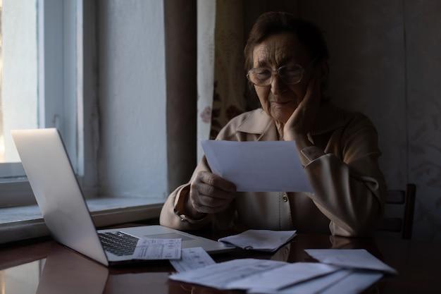 Gepensioneerde leest talloze kranten en is erg gefocust. senior vrouw die belastingen thuis berekent. gepensioneerde vrouw die haar binnenlandse rekeningen berekent. zakelijk, sparen, lijfrenteverzekering, leeftijd en mensenconcept