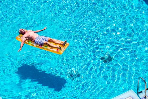 Gepensioneerde levensstijl mooie man senior leeftijd ontspannen en genieten van het blauwe water zwembad slapen op een oranje gekleurde trendy lilo in zomervakantie vakantie