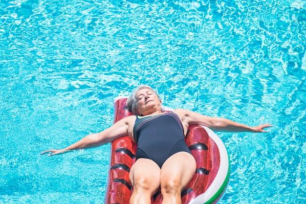 Gepensioneerde levensstijl mooie vrouw senior leeftijd ontspannen en genieten van het blauwe water zwembad slapen op een rode watermeloen trendy lilo in zomervakantie vakantie