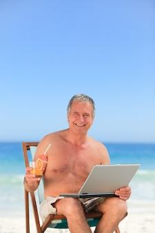 Gepensioneerde man aan het werk op zijn laptop op het strand