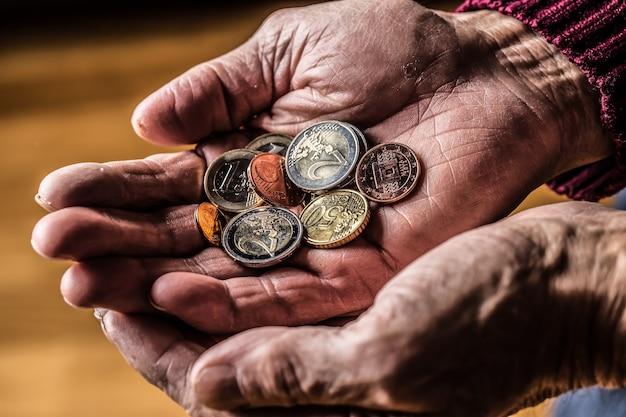 Gepensioneerde man die euromunten in handen houdt. thema lage pensioenen.