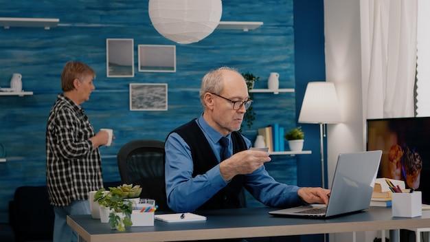 Gepensioneerde man die online betaalt met creditcard op laptop die vanuit huis werkt. senior persoon die online winkelt, rekeningen betaalt, e-commercetransacties doet met behulp van moderne technologie via internet