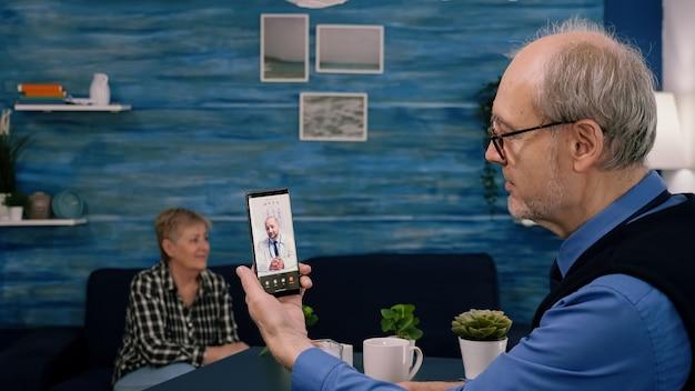 Gepensioneerde man die smartphone vasthoudt tijdens online consult, luisterend naar jonge arts-arts die in de woonkamer zit