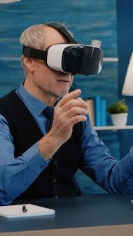 Gepensioneerde man die virtual reality ervaart met behulp van vr-headset in de woonkamer die vanuit huis werkt