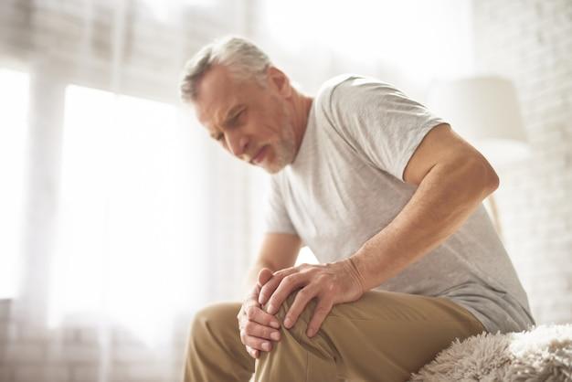 Gepensioneerde man gepensioneerde lijdt aan kniepijn thuis.
